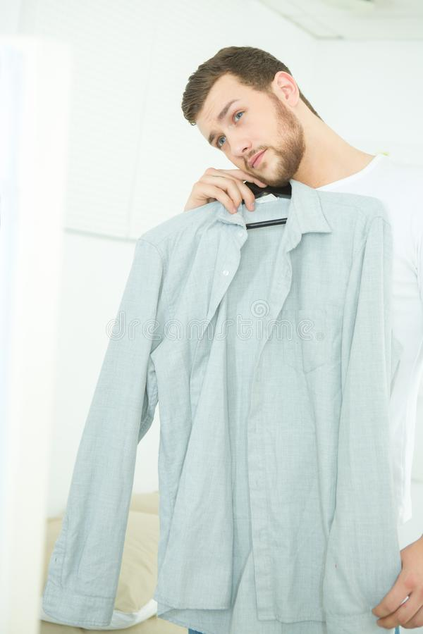 Attractive and strong young man choosing shirt royalty free stock images