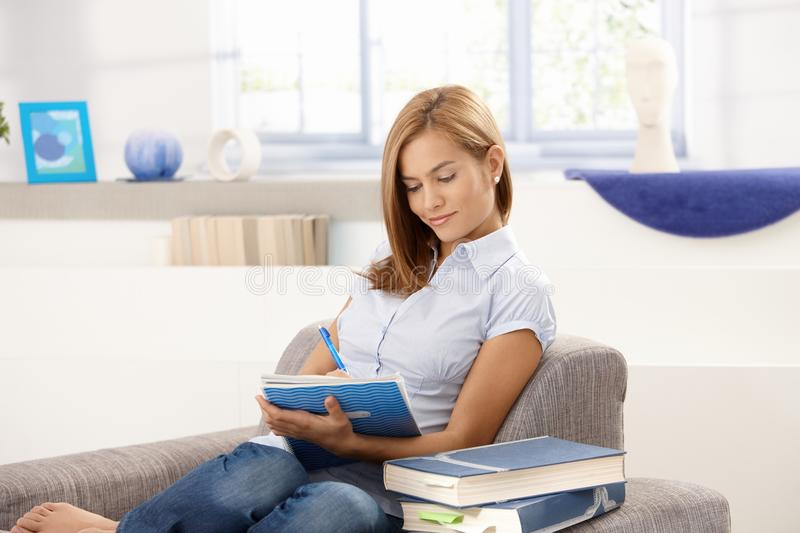 Attractive student doing homework in living room royalty free stock photography