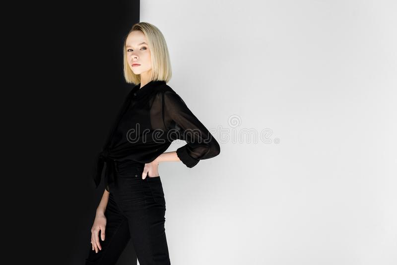 attractive stylish blonde woman in black clothes posing near black royalty free stock images