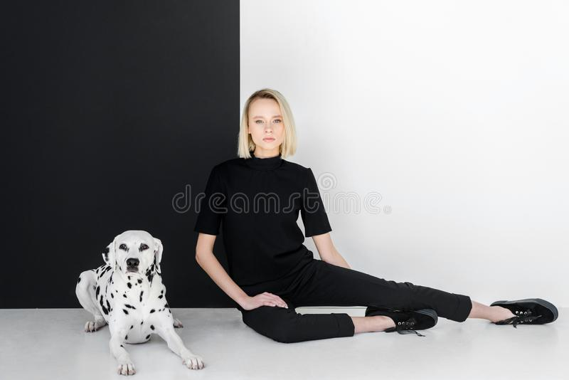 attractive stylish blonde woman in black clothes sitting near black and white wall stock images
