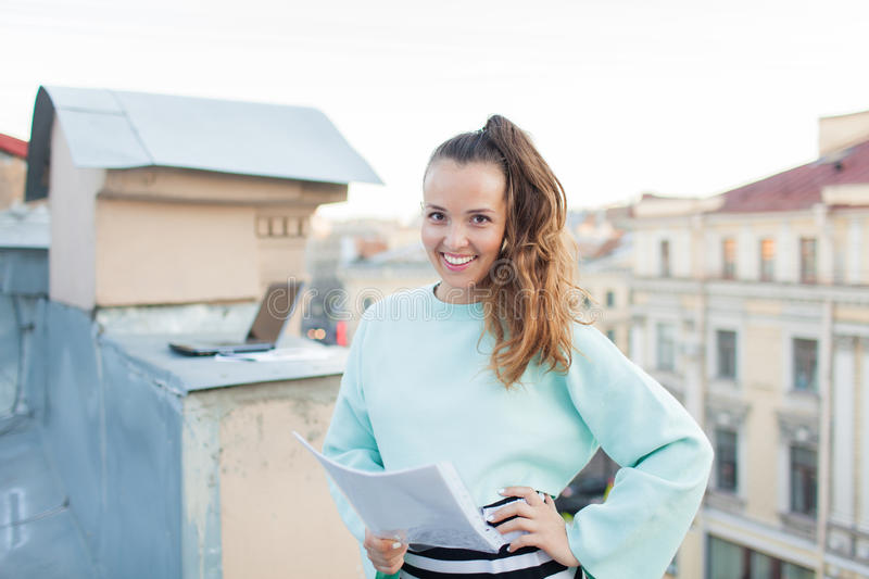 Attractive and stylish business woman holding a document and smiling while standing on the roof of the house in the Old town stock photo