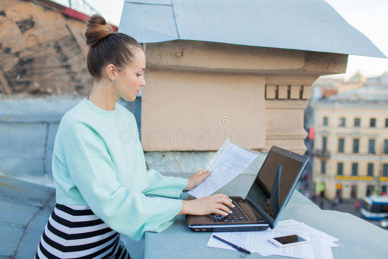 Attractive and stylish businesswoman prepares documents for the roof of the house in the old town standing behind a laptop royalty free stock images