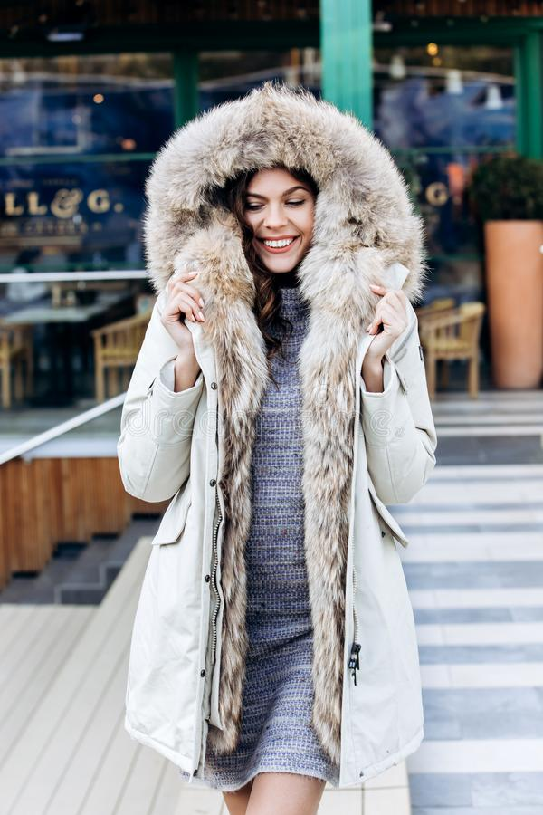 Attractive stylish girl dressed in a knitted dress and a light coat with fur poses in the street stock images
