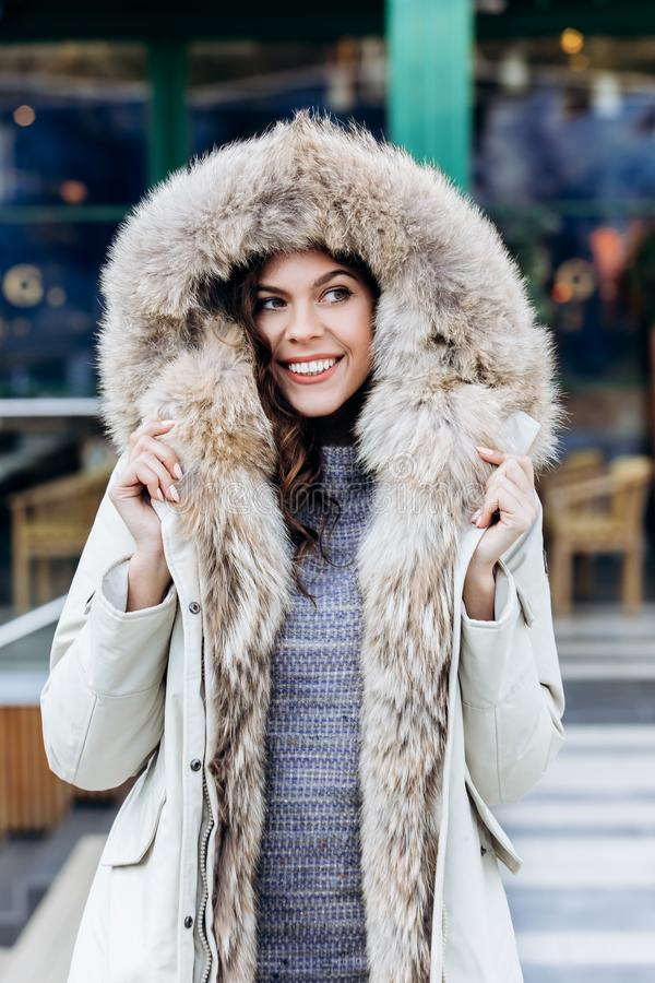 Attractive stylish girl dressed in a knitted dress and a light coat with fur poses in the street stock photos