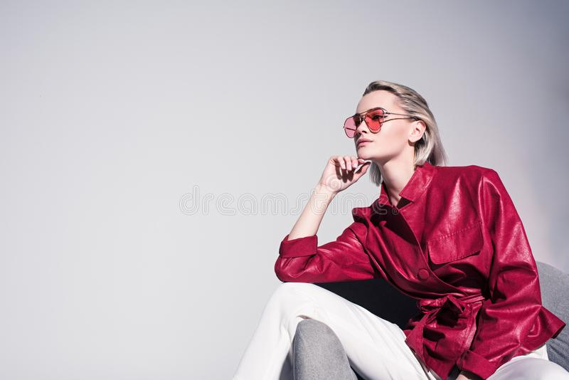 Attractive stylish girl posing on armchair for fashion shoot,. Isolated on grey royalty free stock images