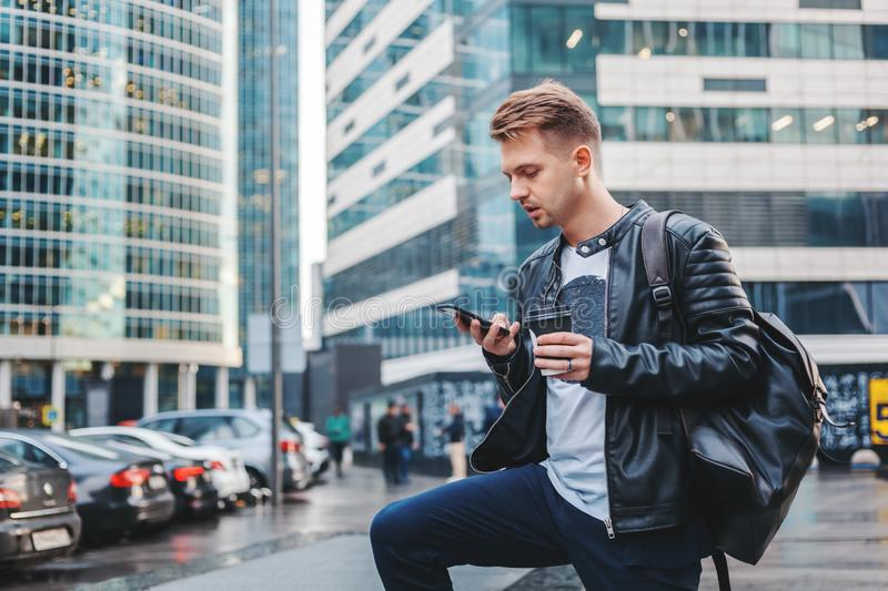 Attractive stylish young man in a leather jacket with a smartphone and take-out coffee in his hands against the backdrop royalty free stock photos