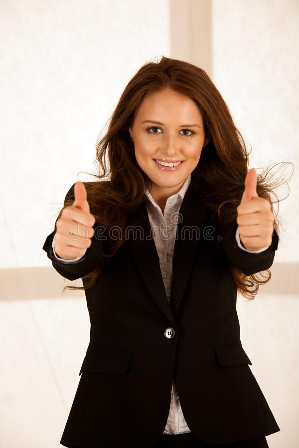 Attractive succesful business woman shows tumb up as a gesture f royalty free stock photography
