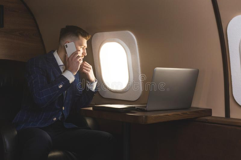 Attractive and successful businessman in an expensive suit working sitting in the chair of his private jet. Attractive and successful businessman in an stock image