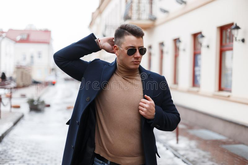 Attractive successful young hipster man in black stylish coat in black sunglasses in vintage knitted sweater posing in the city royalty free stock photo