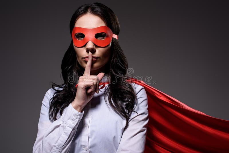 attractive super businesswoman in red cape and mask showing silence gesture royalty free stock photos