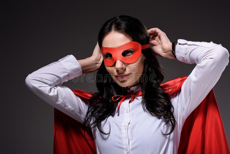 Attractive super businesswoman in red cape tying mask. On black stock photo