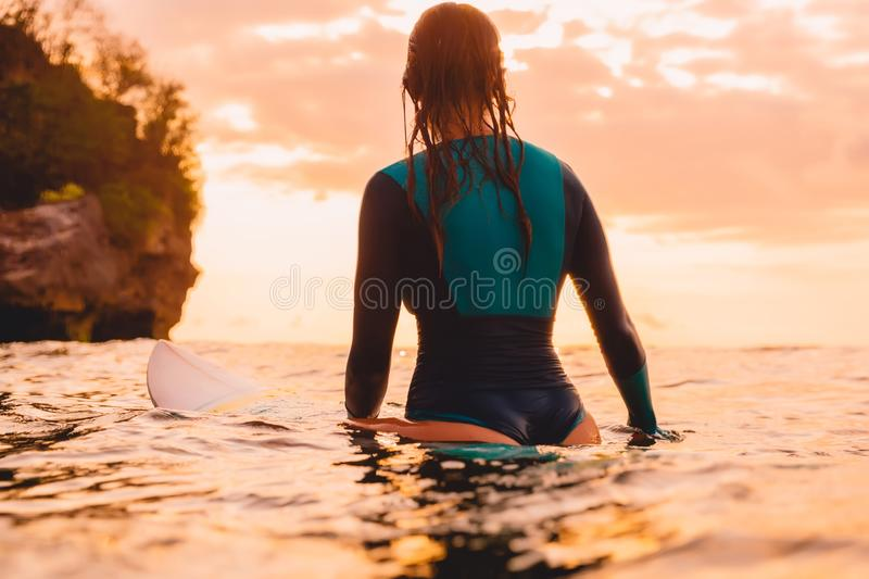 Attractive surf girl with perfect body on surfboard in ocean. Surfing at sunset. Time stock photography