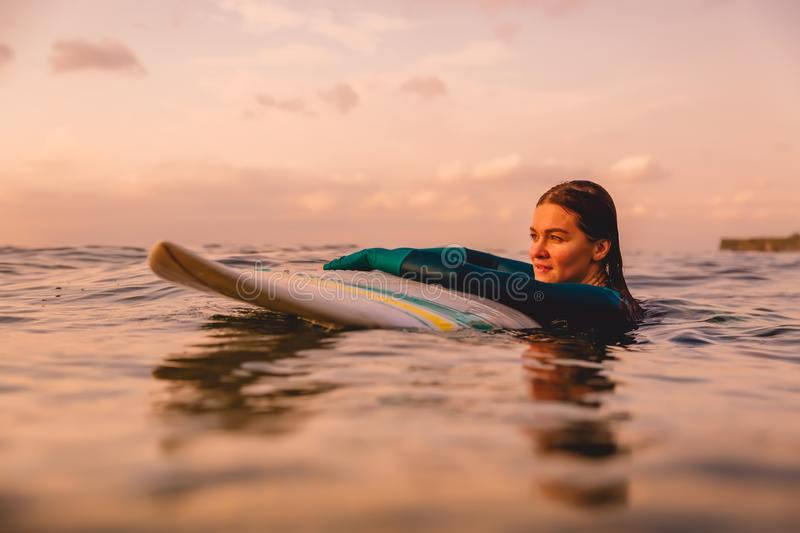 Attractive surf girl with perfect body on surfboard in ocean. Surfing at sunset. Time royalty free stock photos