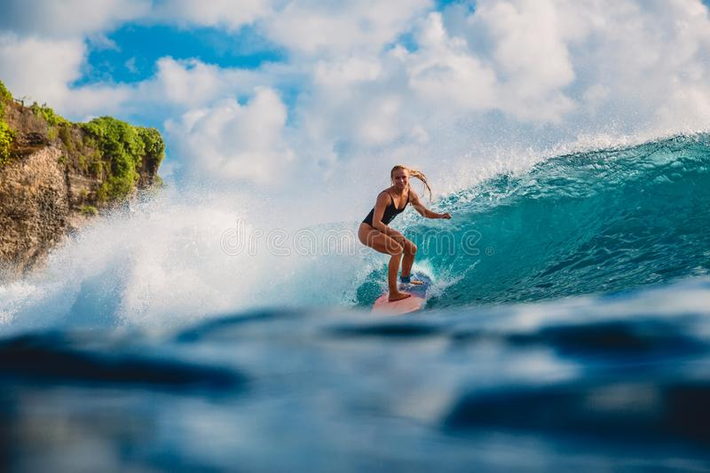 Surf girl on surfboard. Woman in ocean during surfing. Surfer and ocean wave stock photo
