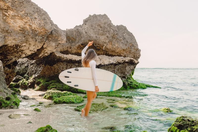 Attractive surf woman with surfboard going to ocean for surfing. Beautiful sporty woman. Attractive surf woman with surfboard going to ocean for surfing royalty free stock photos