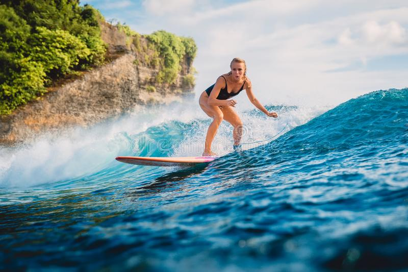 Attractive surf woman on surfboard. Woman in ocean during surfing. Surf girl on surfboard. Woman in ocean surfing royalty free stock image