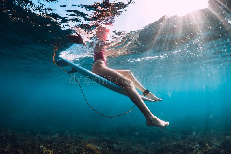 Attractive surfer girl sit at surfboard underwater in ocean. Attractive surfer girl sit at surfboard underwater stock photography