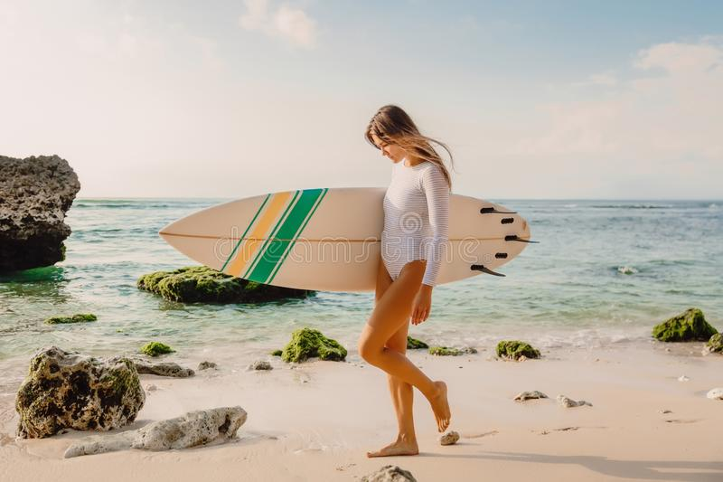 Attractive surfer girl with surfboard at beach. Attractive surfer girl with surfboard on beach royalty free stock images
