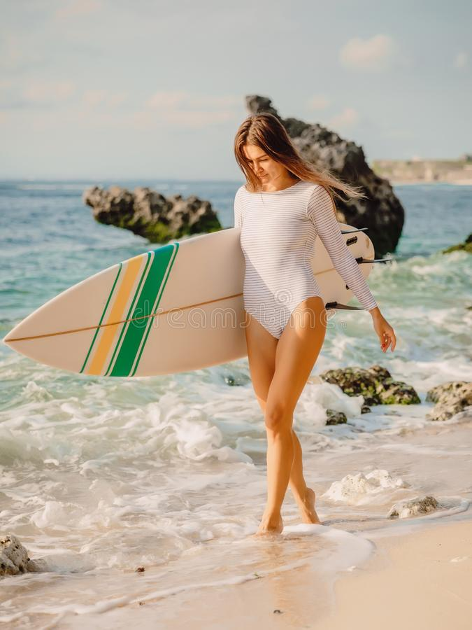 Attractive surfer girl with surfboard at beach. Attractive surfer girl with surfboard on beach royalty free stock photos