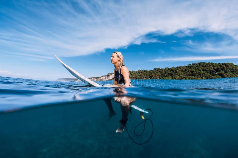Attractive surfer girl at surfboard in ocean, Bali stock photos