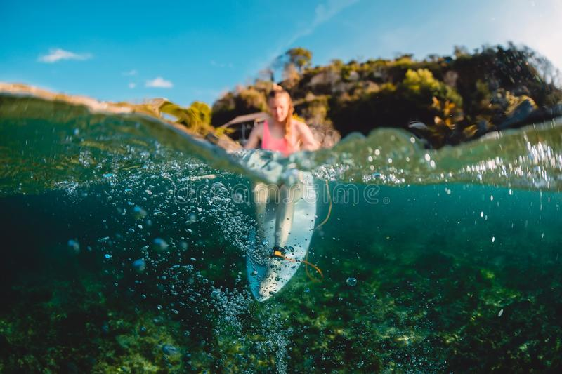 Attractive surfer girl with surfboard. Surfer sit at board. In ocean stock photos