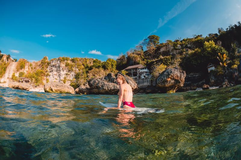 Attractive surfer girl with surfboard. Surfer sit at board. In ocean royalty free stock image