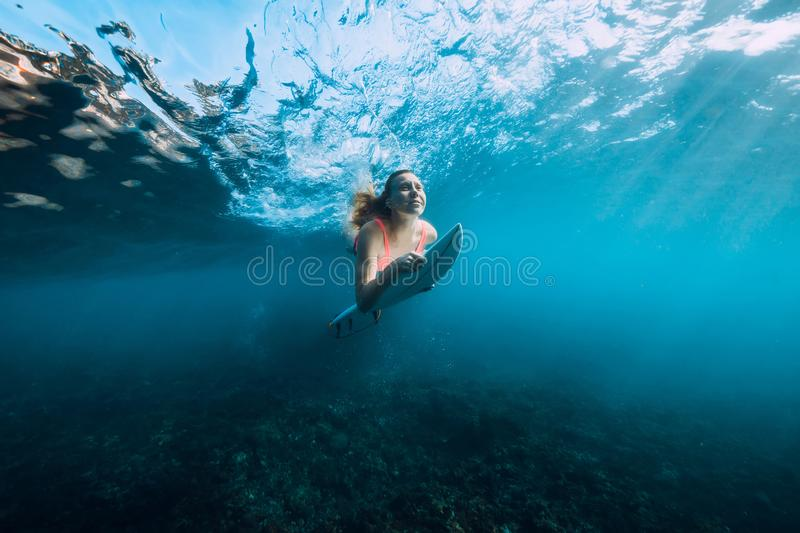Attractive surfer woman in bikini with surfboard dive underwater with under barrel wave. Attractive surfer woman in bikini with surfboard dive underwater with stock photos