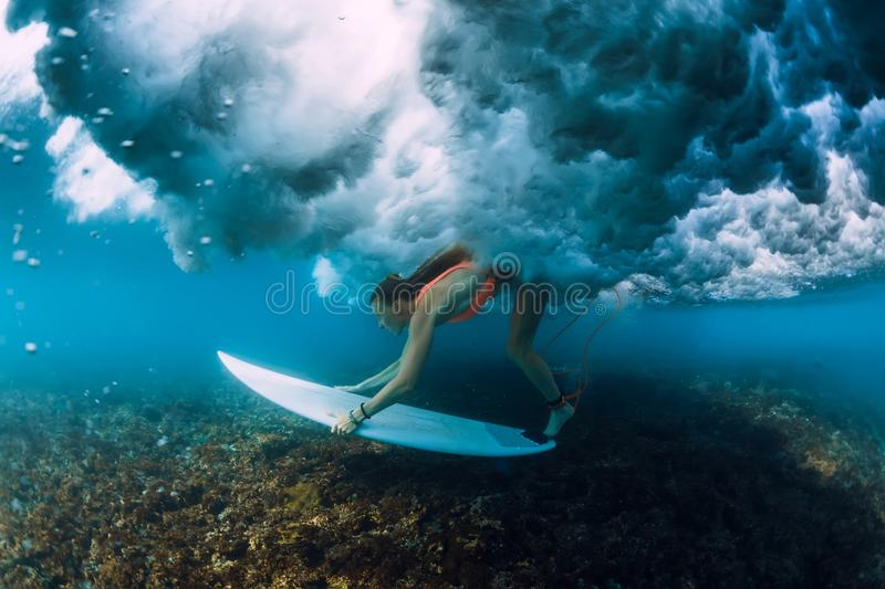 Attractive surfer woman dive under crashing barrel wave. Attractive surfer woman dive under crashing wave stock photography