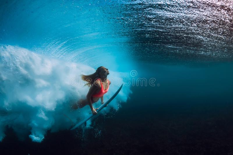 Attractive surfer woman dive underwater with big wave. Attractive surfer woman dive underwater with wave stock photography