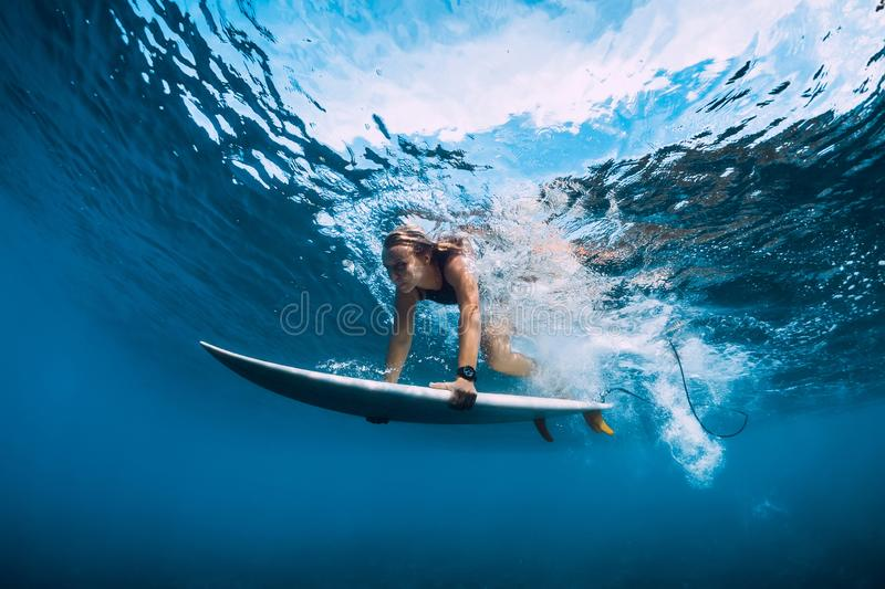 Attractive surfer woman dive underwater. Surfgirl under wave royalty free stock photography