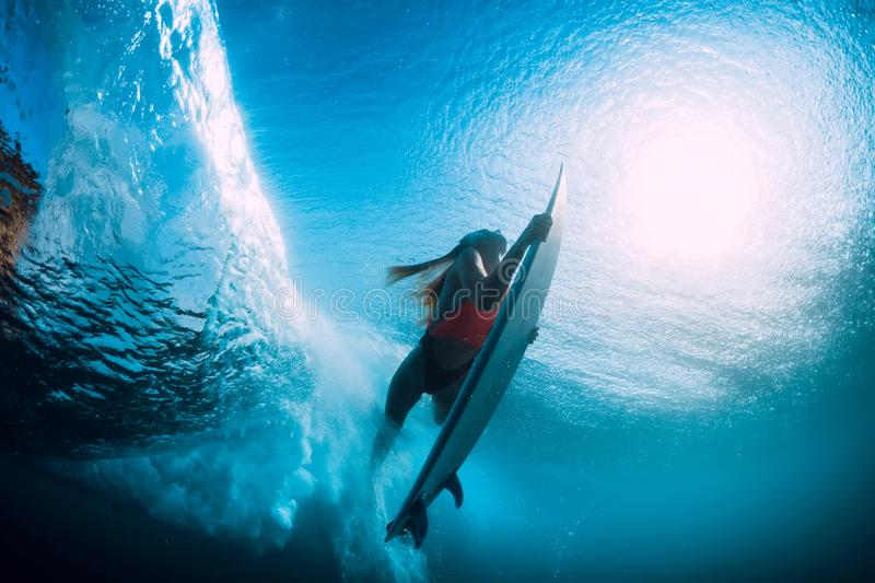Attractive surfer woman dive underwater with under barrel wave. Attractive surfer woman dive underwater with under wave stock image