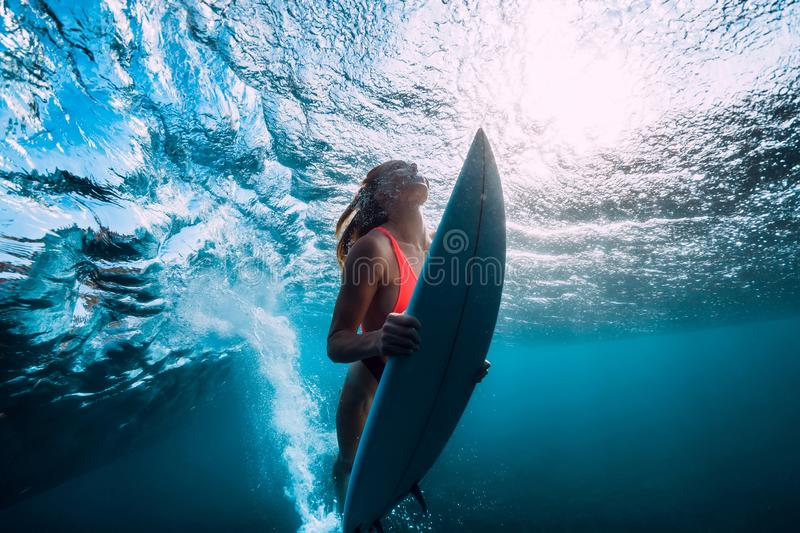 Attractive surfer woman dive underwater with under ocean wave. Attractive surfer woman dive underwater with under wave royalty free stock images