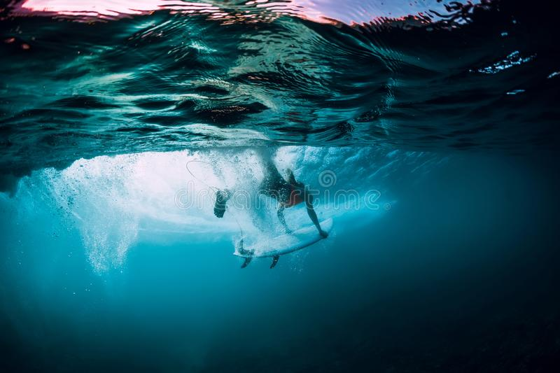 Attractive surfer woman dive underwater with under barrel wave. Attractive surfer woman dive underwater with under wave royalty free stock photography