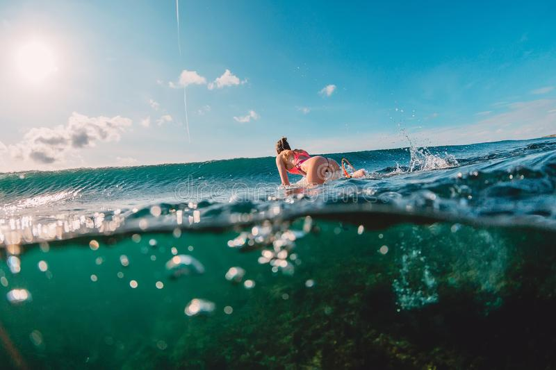 Attractive surfer woman in ocean and wave. Surf girl make duck dive. Attractive surfer woman in ocean and wave stock images