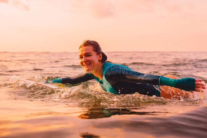 Attractive surfer woman on a surfboard swim in ocean. Surfing at sunset. Attractive surfer woman on a surfboard swim in sea royalty free stock photography