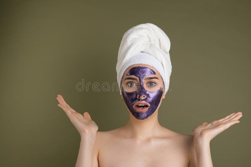 Attractive surprised young woman with purple face mask and shower towel on her head. With raised palms, looking at camera on green background stock photos