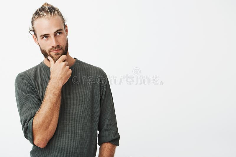 Attractive swedish guy with stylish hair and beard in grey shirt holding his chin and thoughtfully looking aside royalty free stock photos