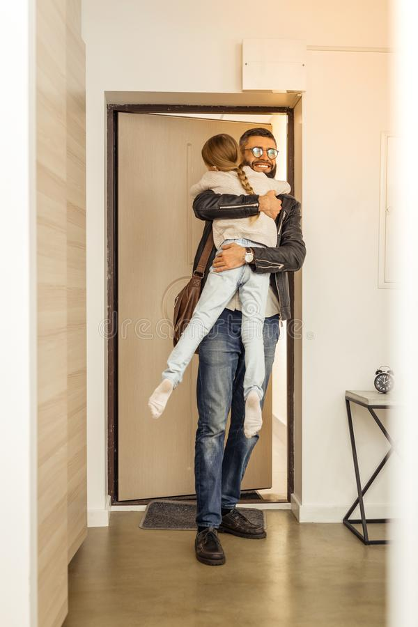 Attractive tall short-haired bearded man from generation Y holding his daughter stock photography