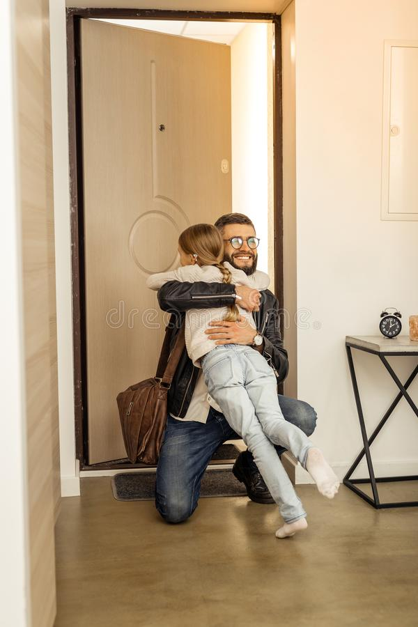 Attractive tall short-haired bearded man from generation Y hugging his daughter stock photo