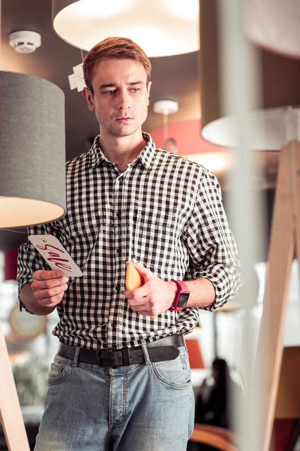 Attractive tall young mister concernedly standing in lamp store royalty free stock image
