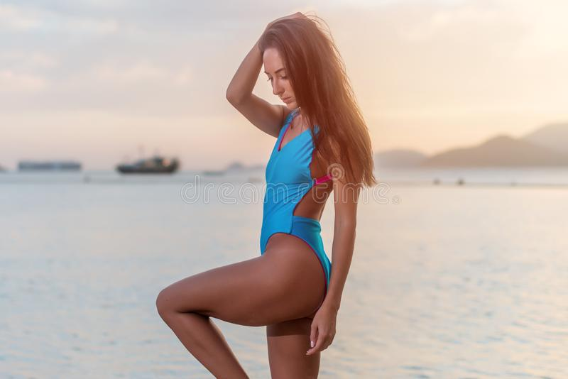 Attractive tanned female tourist in swimwear standing on seashore at seaside resort. Attractive tanned female tourist in swimwear standing on seashore at stock photo