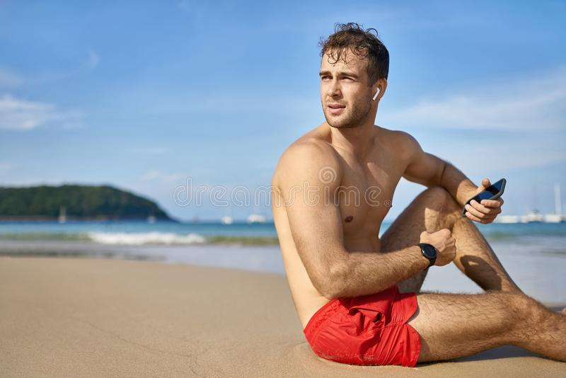 Tanned guy on beach. Attractive tanned man sits on the sand beach on the sunny background of the sea with white boats and the blue sky. He wears a red swim stock image