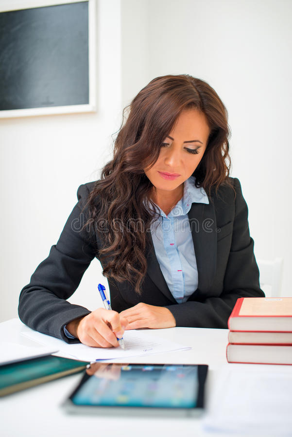 Attractive teacher. Attractive teacher checking tests at school stock photos