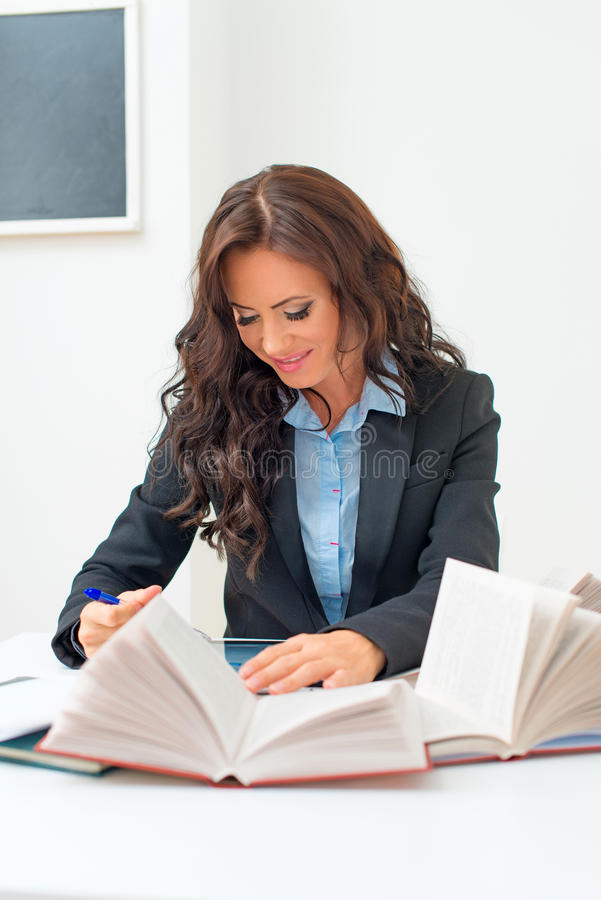 Attractive teacher. Attractive teacher checking tests at school stock photography
