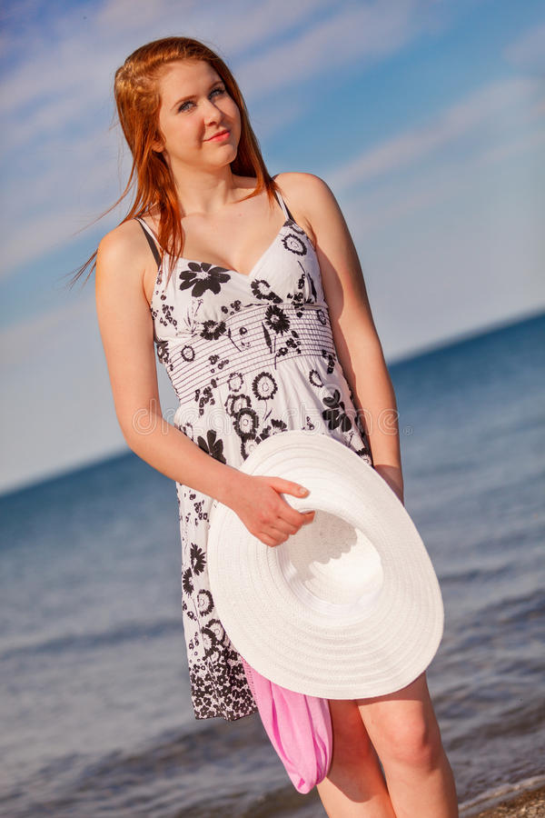An attractive teen at the beach with a white hat stock image