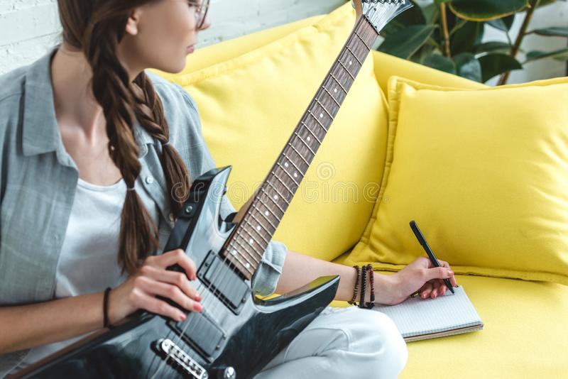 Attractive teen girl playing electric guitar and writing song stock photo