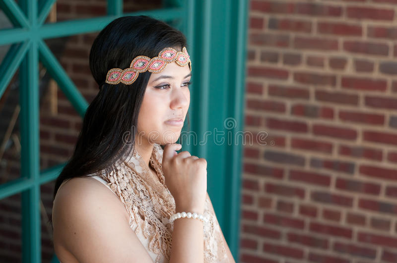 Attractive teen looking off in distance. Outdoor shot of attractive teen girl looking way from camera royalty free stock photography