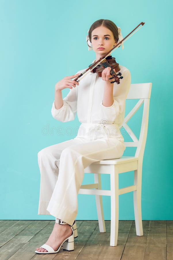 attractive teen musician playing violin and sitting on chair stock photos