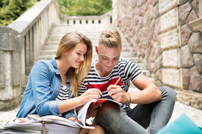 Attractive teenage student couple in front of university studying. royalty free stock images