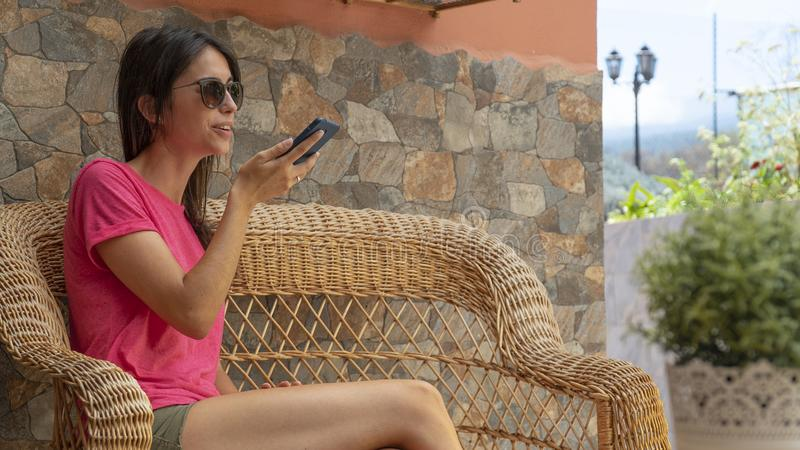 Attractive teenager Using Voice Recognition App On Smart Phone. Young woman recording an audio message in cellphone. Girl royalty free stock photography